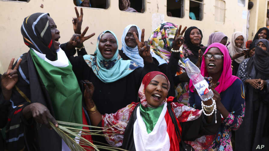 FILE - Sudanese pro-democracy supporters celebrate a final power-sharing agreement with the ruling military council, in Khartoum, Aug. 17, 2019. For the first time in three decades, Sudan has charted a path out of military rule.