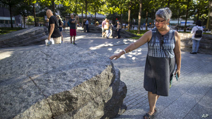 A visitor touches one of the granite slabs at the 9/11 Memorial Glade at the National September 11 Memorial & Museum in New York, Aug. 29, 2019.