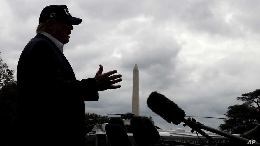 With cloudy skies in Washington, President Donald Trump speaks to the media as he returns to the White House from Camp David, Sunday, Sept. 1, 2019, in Washington.