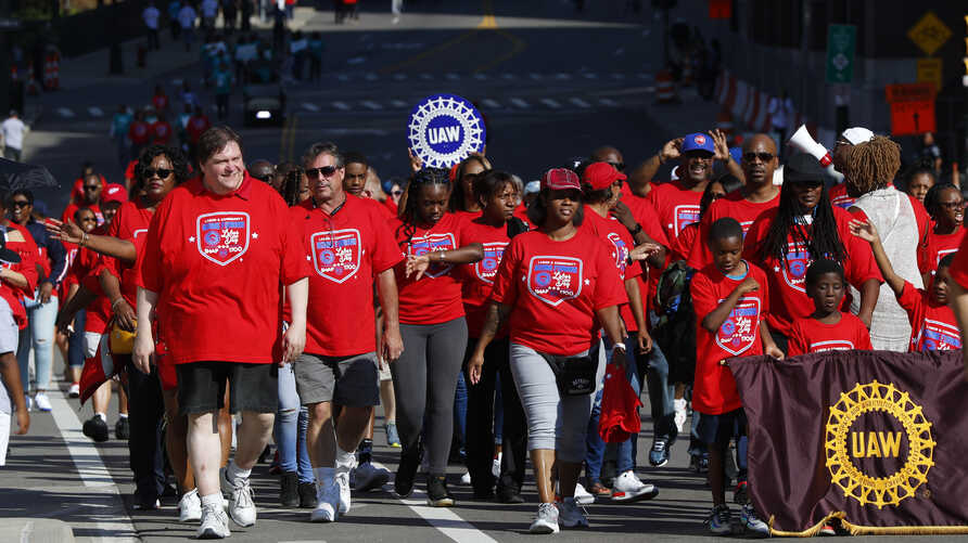 Members of the United Auto Workers walk in the Labor Day parade in Detroit, Sept. 2, 2019. The union's contract with GM has expired and a strike could happen as early as Sunday.