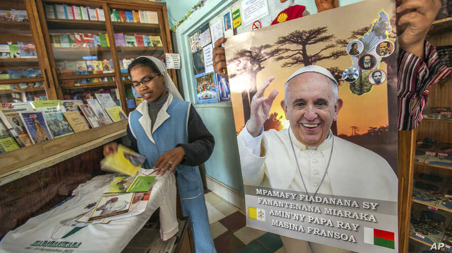A nun shops in a store offering Pope paraphernalia in Antananarivo, Sept. 3, 2019.