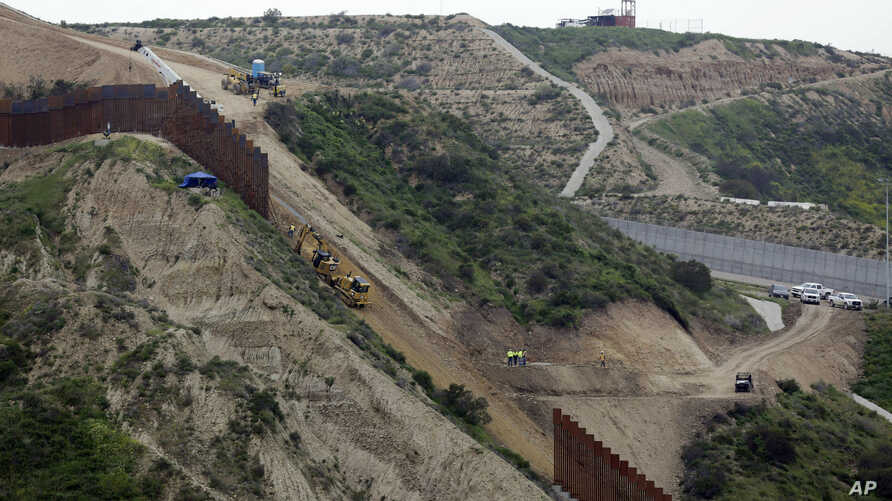 In this March 11, 2019 photo, construction crews replace a section of the primary wall separating San Diego, above right, and Tijuana, Mexico, below left, seen from Tijuana, Mexico.