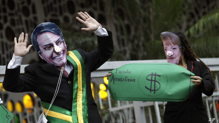 Demonstrators wear masks of Brazil's President Jair Bolsonaro, left, and Germany's Chancellor Angela Merkel during a protest in defense of the Amazon in Rio de Janeiro, Brazil, Sept. 5, 2019. Germany has suspended a line of funding for Amazon projects.