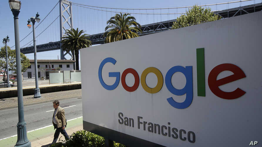FILE - A man walks past a Google sign in San Francisco, May 1, 2019.
