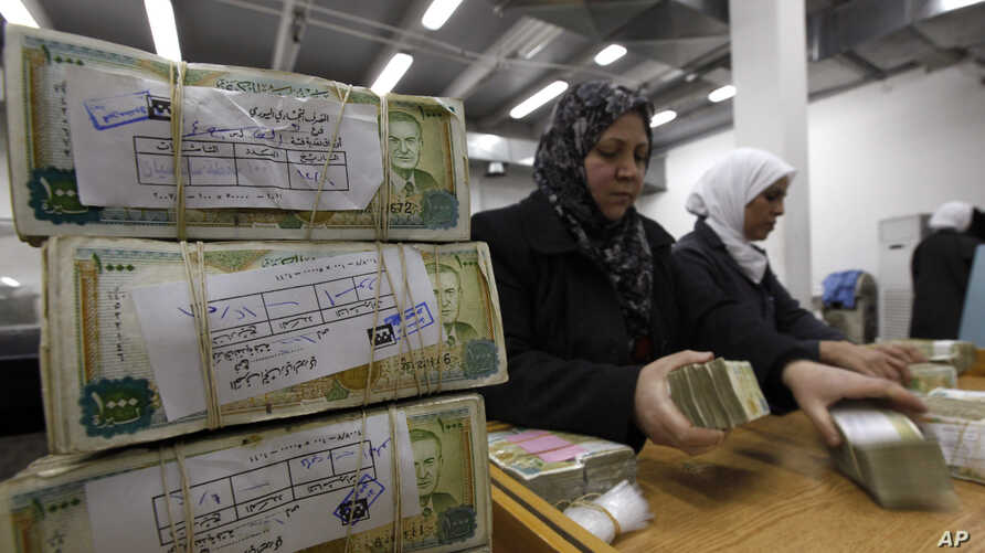 FILE - Employees stack Syrian currency in the Central Bank, in Damascus, Syria, Jan. 13, 2010.