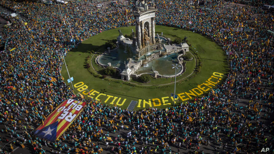Protesters hold esteladas or independence flags as they take part in a demonstration during the Catalan National Day in Barcelona, Spain, Sept. 11, 2019.