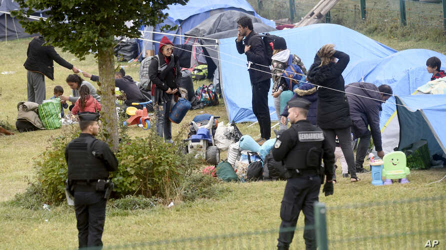 French police officers watch migrants packing their belongings in a camp of Grande Synthe, northern France, Tuesday, Sept.17, 2019.