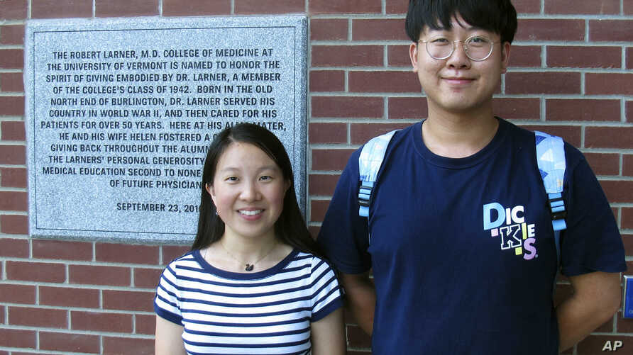 Chinese graduate students Zhaojin Li, left, and Pengfei Liu, pose in front of the entrance to the Robert Larner College of Medicine at the University of Vermont in Burlington, Vermont, Aug. 16, 2019.