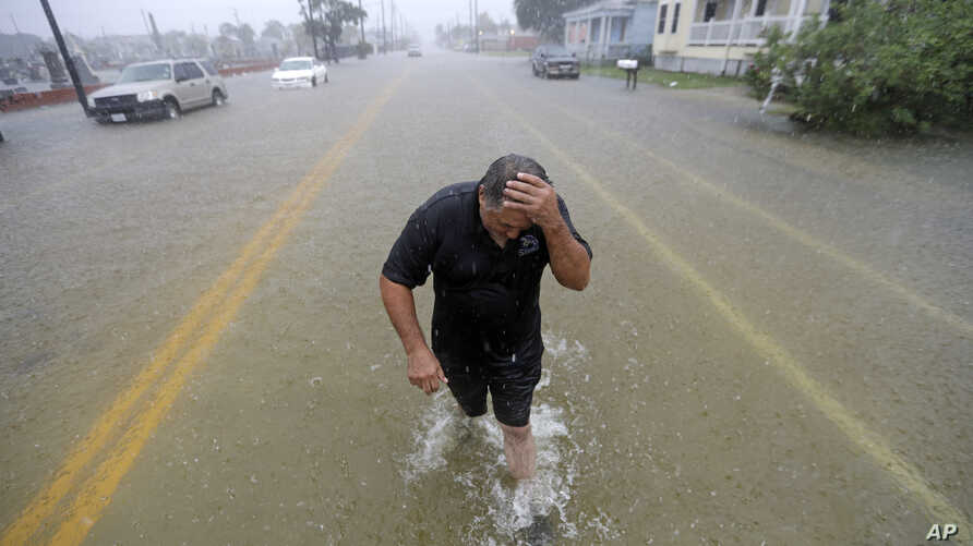 Angel Marshman wades through floodwaters after trying to start his flooded car in Galveston, Texas, Sept. 18, 2019.