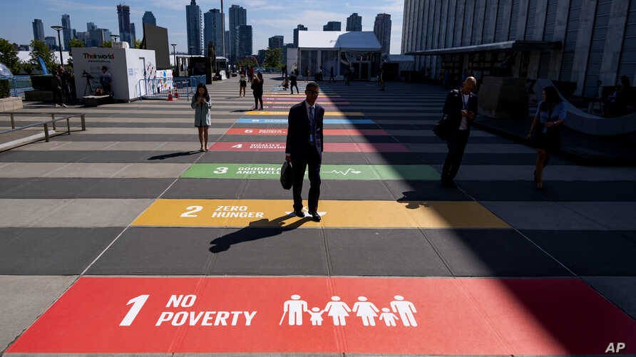 People walk along a plaza at United Nations Headquarters, Sept. 21, 2019.