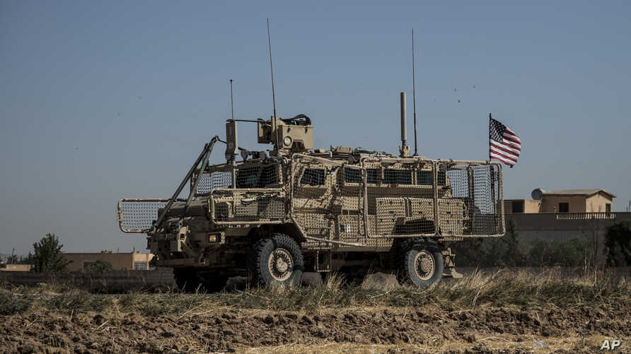 """An American armored vehicle patrols with Turkish forces, as they conduct their second joint ground patrol in the """"safe zone"""" on the Syrian side of the border with Turkey, in Rahaf village, near the town of Tal Abyad, northeastern Syria, Sept. 24, 2019."""