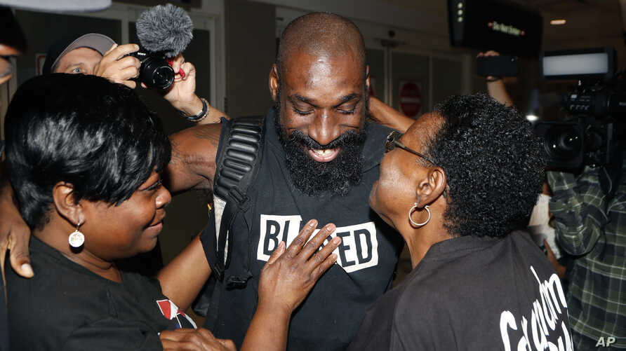 Wendell Brown hugs relatives after his arrival at the Detroit Metropolitan Airport in Romulus, Michigan, Sept. 25, 2019.