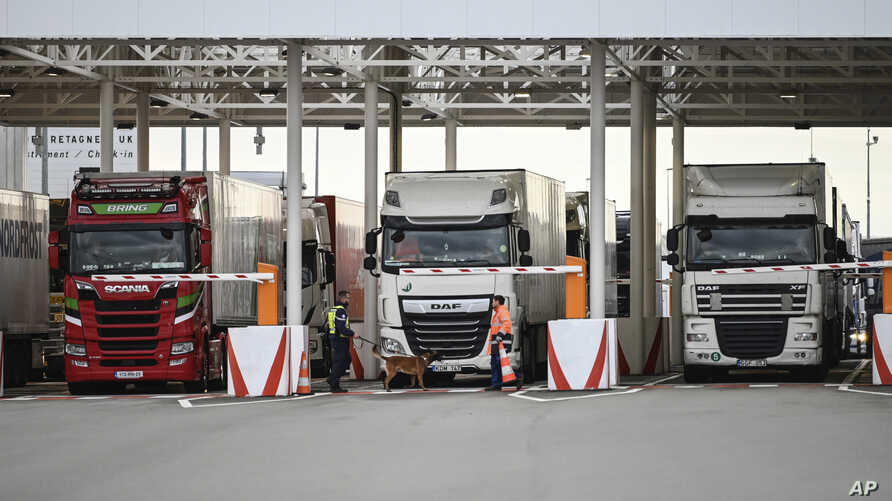 FILE - An employee of Eurotunnel and his dog check trucks on their way to Britain during a testing day in case of no-deal Brexit, at the exit of the Channel tunnel in Calais, northern France, Sept. 17, 2019.