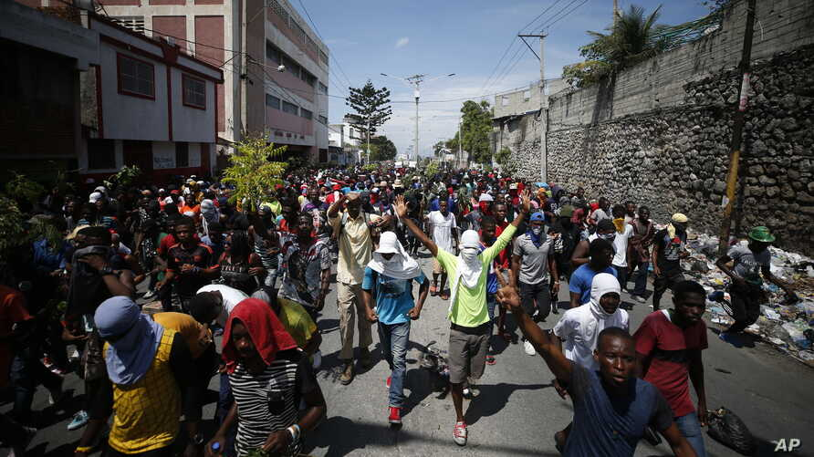 Haitians respond to a nationwide push to block streets and paralyze the country's economy as they press for President Jovenel Moise to give up power, in Port-au-Prince, Haiti, Monday, Sept. 30, 2019.