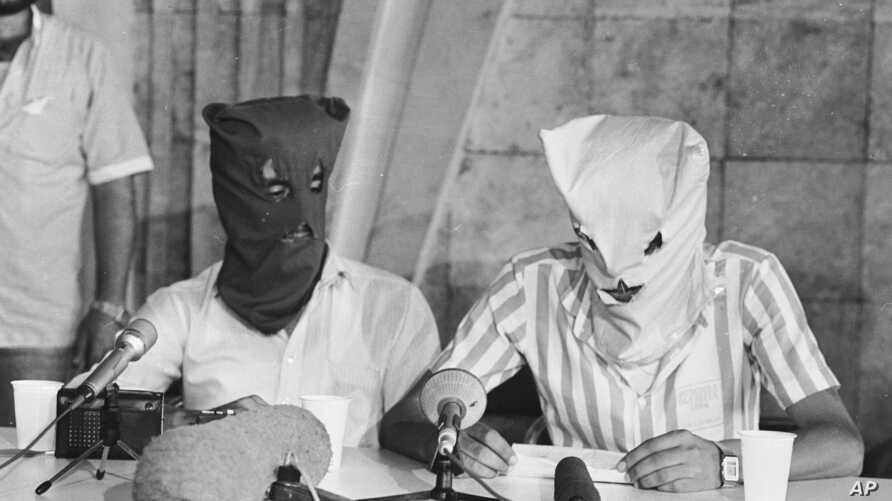 FILE - Two hooded Shiite Muslim men, who were identified as the original hijackers of the TWA jet seized on a flight from Athens to Rome, July 14, 1985, and commandeered to Beirut airport, hold a news conference at the Beirut airport, July 30, 1985.