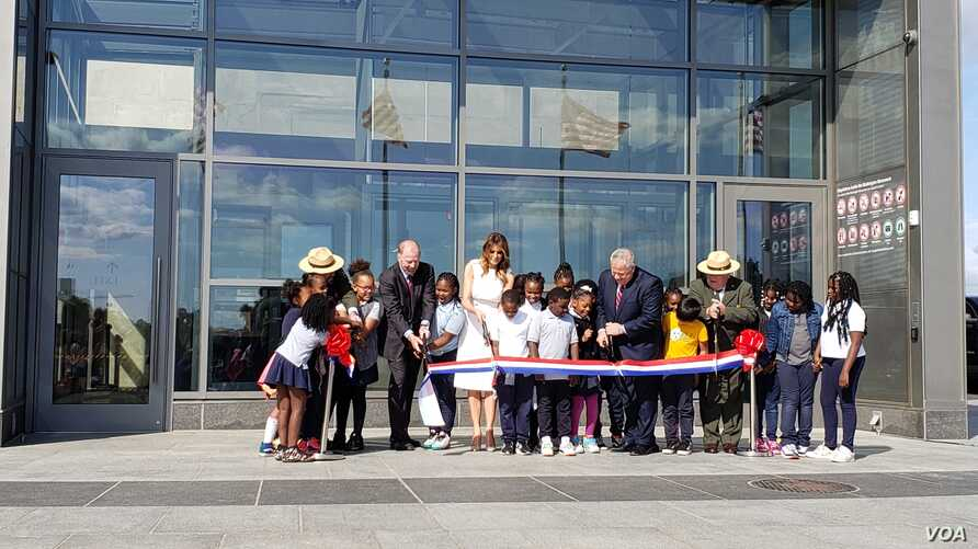 First lady Melania Trump, center, and Department of Interior assistant secretary Rob Wallace, left, participate in a ribbon-cutting ceremony with students from Amidon-Bowen Elementary School in Washington to re-open the Washington Monument, Sept. 19, 2019.