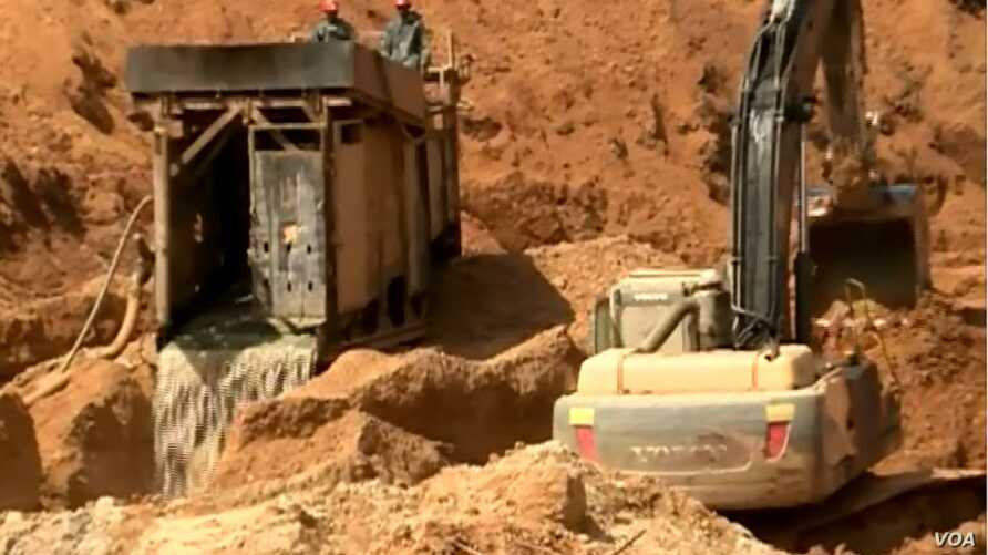 More than 100 mining companies have operations in an area near Meiganga, Cameroon. They use tractors and equipment that clean stones and sift soil, allowing them to detect gold faster than locals who use manual tools. (M. Kindzeka/VOA)