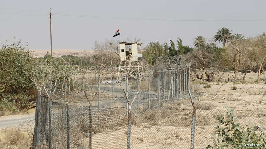 FILE - An Iraqi border policeman stands guard on a watch tower on the Iraqi-Syrian border at the Abu Kamal border crossing, the main border post between Iraq and Syria, Sept. 8, 2012.