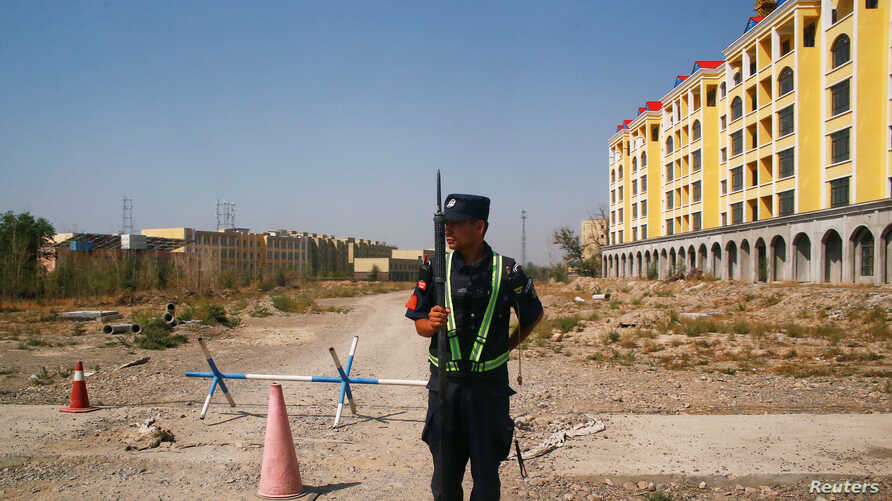 FILE - A Chinese police officer takes his position by the road near what is officially called a vocational education center in Yining in Xinjiang Uighur Autonomous Region, China, Sept. 4, 2018.