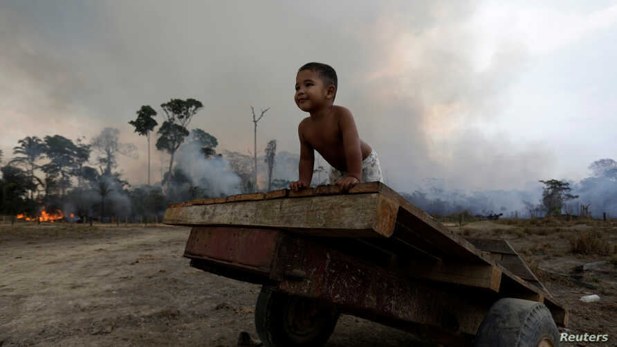 FILE - Jose, 2, plays while a fire burns a tract of Amazon jungle as it is cleared by loggers and farmers near Porto Velho, Brazil, Aug. 27, 2019.