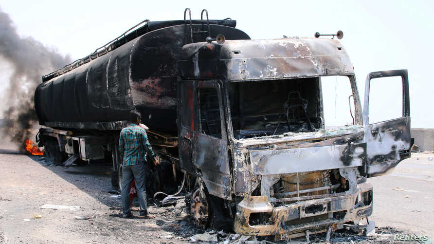 A man inspects an oil tanker truck set ablaze during recent clashes between Yemeni southern separatists and government forces near Aden, Yemen, August 30, 2019.