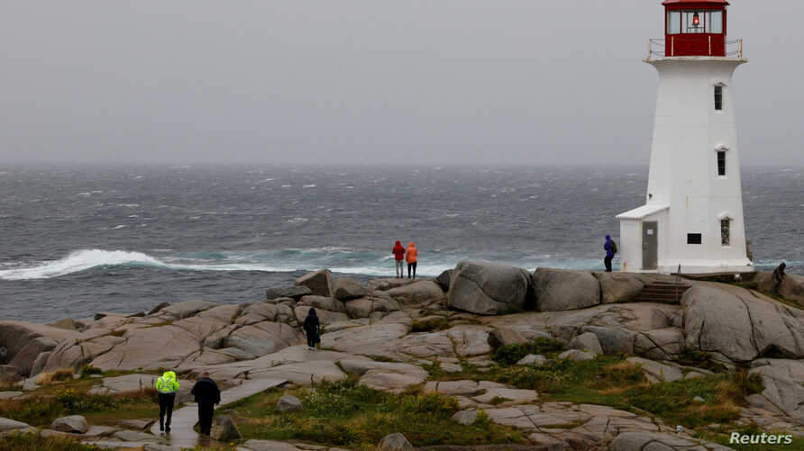 Two Royal Canadian Mounted Police officers walk toward the Peggy's Cove Lighthouse to warn individuals of the dangers during the arrival of Hurricane Dorian in Peggy's Cove, Nova Scotia, Sept. 7, 2019.