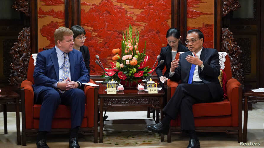 Chinese Premier Li Keqiang talks with Executive Vice President and Head of International Affairs at the U.S. Chamber of Commerce Myron Brilliant, during a meeting with a group of U.S. entrepreneurs at Zhongnanhai in Beijing, China, Sept. 10, 2019.