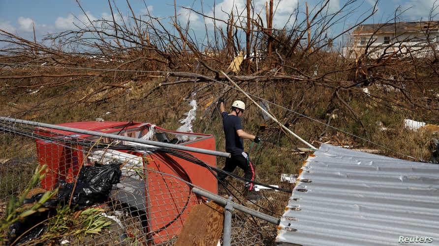 A member of the Canadian Burnaby Firefighters Search & Rescue Task Force searches for victims after Hurricane Dorian hit the Abaco Islands in Marsh Harbour, Bahamas, Sept. 11, 2019.