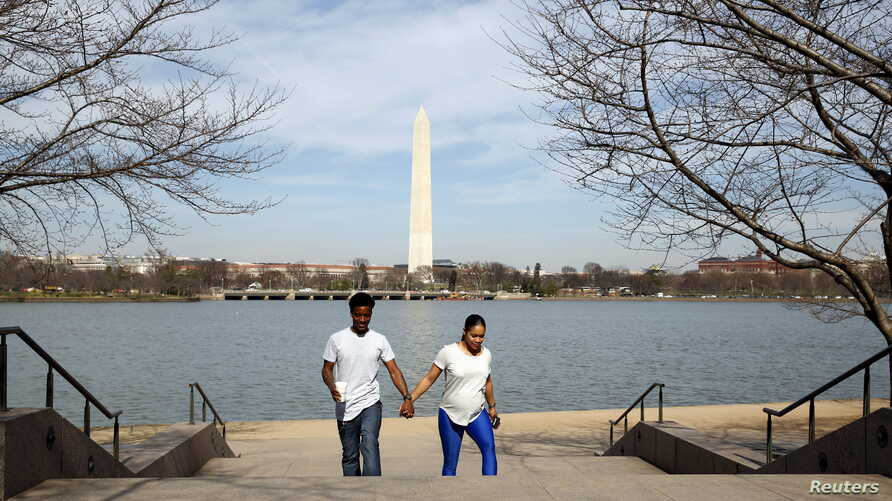 With the Washington Monument in the background, a couple walks hand in hand along the Tidal Basin  in Washington, March 9, 2016.