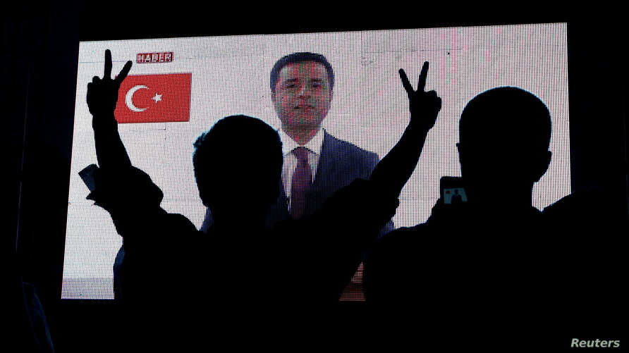 FILE - Supporters of Turkey's main pro-Kurdish Peoples' Democratic Party (HDP) watch the jailed former leader Selahattin Demirtas in a television appearance in Istanbul, Turkey, June 17, 2018.