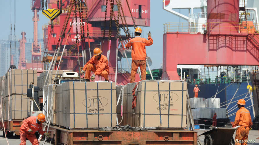 FILE - Workers load goods for export onto a crane at a port in Lianyungang, Jiangsu province, China, June 7, 2019.