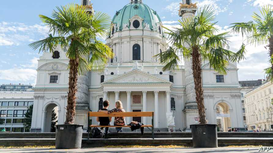 FILE - People sit on a bench in front of the Karlskirche, or St. Charles' church, on the Karlsplatz square in the Austrian capital, Vienna, Oct. 5, 2017.