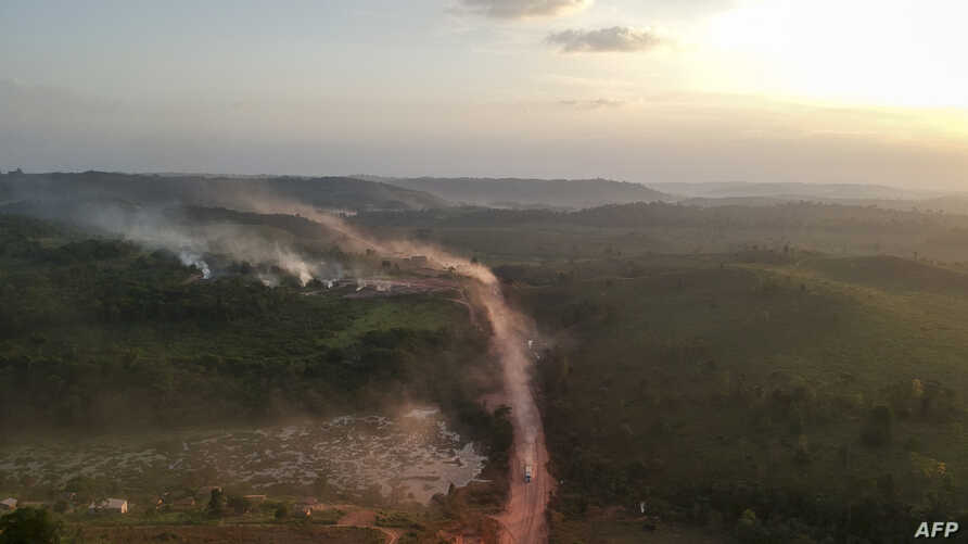 """In this aerial view the red dust of the BR230 highway, known as """"Transamazonica,"""" mixes with fires at sunset in the agriculture town of Ruropolis, Para state, northern Brazil, Sept. 6, 2019."""
