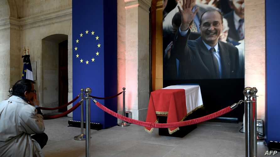 A man looks at the coffin of former French President Jacques Chirac lying in state during a memorial ceremony at the Saint-Louis-des-Invalides cathedral at the Invalides memorial complex in central Paris, Sept. 29, 2019.