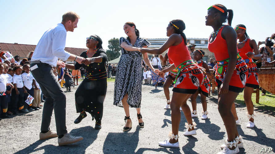 "Prince Harry, Duke of Sussex and Meghan, Duchess of Sussex, dance during a visit to the ""Justice desk"", an NGO in the township of Nyanga in Cape Town, as they begin their tour of the region."