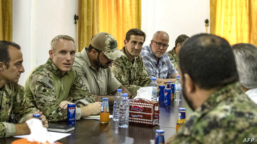 Members of the US-led coalition forces meet with local forces from the Tal Abyad military council in the northern Syrian town of Tal Abyad, on Sept. 15, 2019