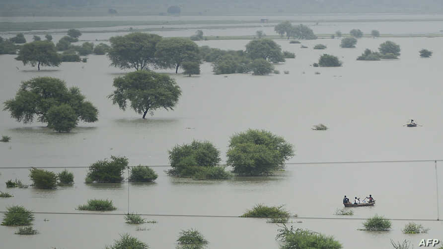 FILE - An aerial view shows villagers using boats to cross a flooded Ganges river, in Allahabad, Uttar Pradesh, India, Aug. 21, 2019.