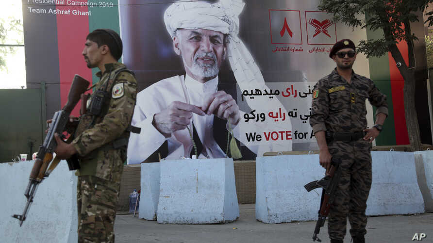 Afghan security forces stand guard in front of an election poster for presidential candidate Ashraf Ghani in Kabul, Afghanistan, Sept. 23, 2019.