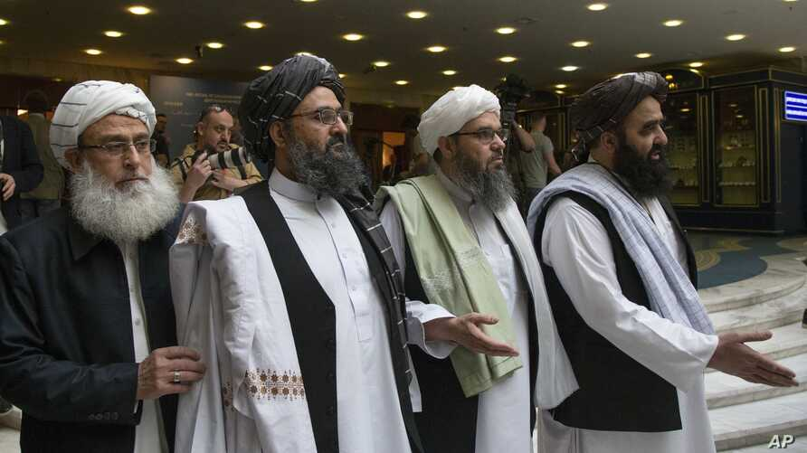 FILE - In this May 28, 2019 file photo, Mullah Abdul Ghani Baradar, the Taliban group's top political leader, second left, arrives with other members of the Taliban delegation for talks in Moscow, Russia.