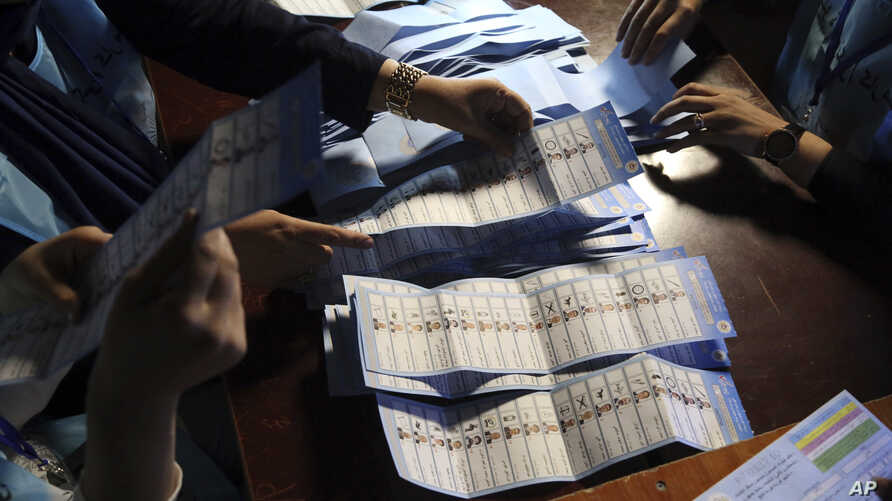 Election workers count ballots at a polling station in Kabul, Afghanistan, Sept. 28, 2019.