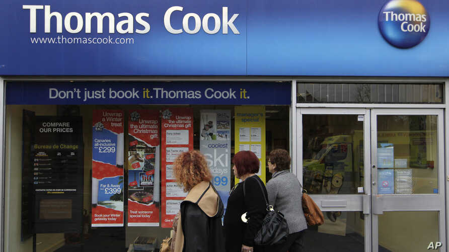 FILE - People walk-by a branch of Thomas Cook travel agent in Borehamwood, north London,  Nov. 22, 2011.