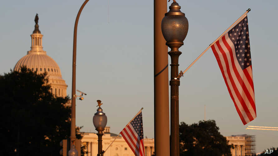 Flags fly at sunset with 51 instead of the usual 50 stars, along Pennsylvania Ave., part of a display in support of statehood for the District of Columbia, Sept. 15, 2019, in Washington.