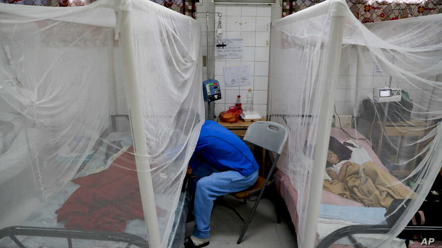 A relative visits a patient receiving treatment for dengue at University School Hospital in Tegucigalpa, Honduras, Aug. 20, 2019.
