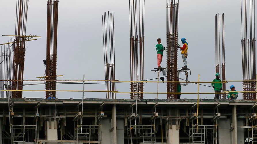 Construction workers stand on scaffolding around metal rods of a new pillar as they add more floors to a building project in suburban Paranaque city, south of Manila, Philippines, Jan. 26, 2017.