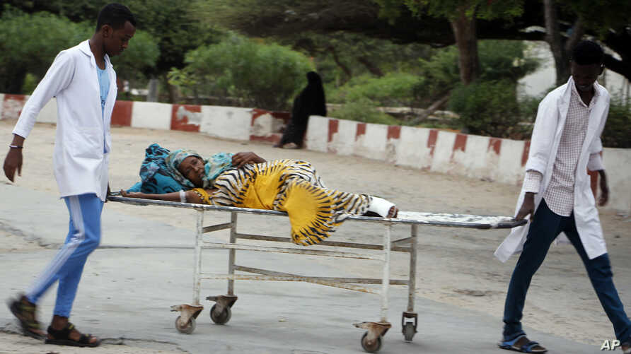 FILE - Medical workers help a civilian on stretcher who was wounded in a suicide bomb attack, at Madina hospital in Mogadishu, Somalia, July 24, 2019.