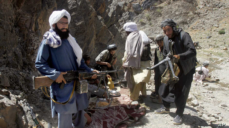 FILE - Taliban fighters prepare to guard a gathering, in Shindand district of Herat province, Afghanistan, May 27, 2016.