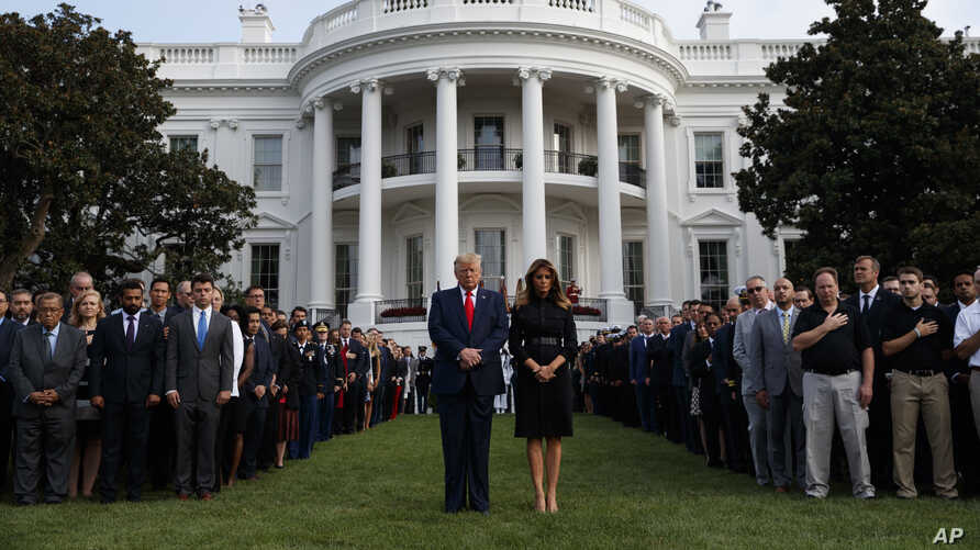 President Donald Trump and first lady Melania Trump participate in a moment of silence honoring the victims of the Sept. 11, 2001, terrorist attacks, on the South Lawn of the White House, in Washington, Sept. 11, 2019.