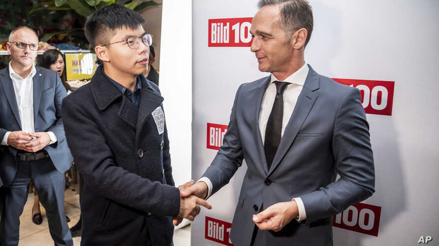 German Foreign Minister Heiko Maas, right, and Hong Kong activist Joshua Wong shake hands during a reception for German newspaper Bild, in Berlin, Germany, Sept. 9, 2019.