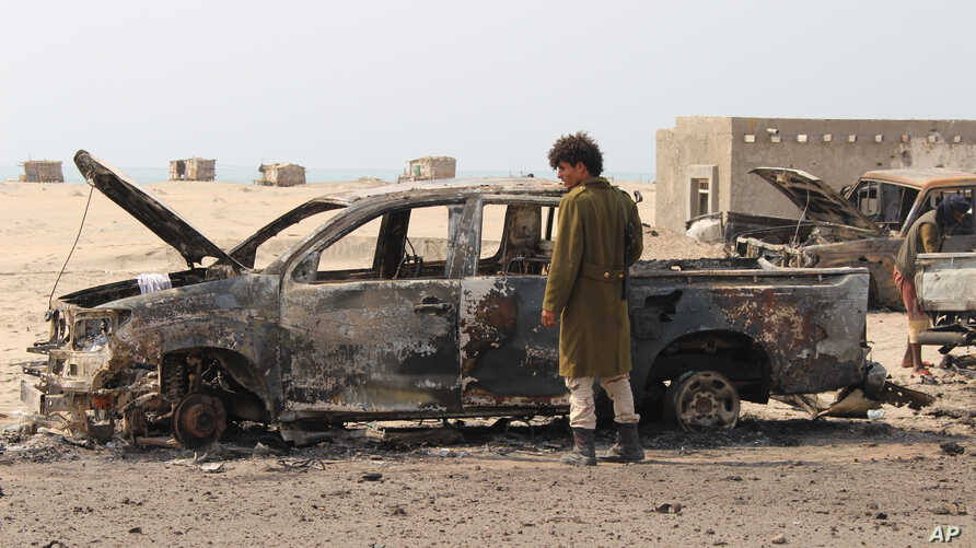 A Yemeni southern separatist fighter inspects the wreckage of government forces vehicles destroyed by UAE airstrikes near Aden, Yemen, Friday, Aug. 30, 2019