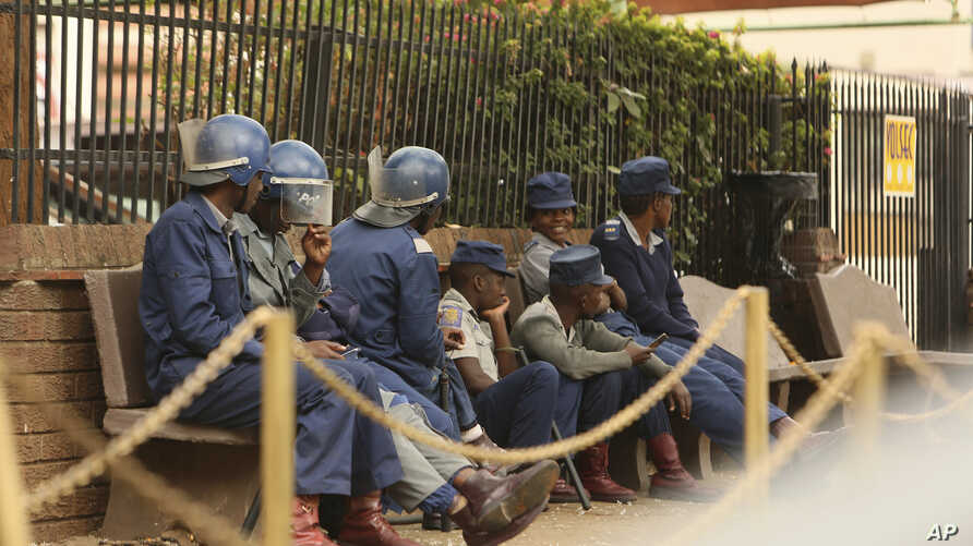 Zimbabwe riot police sit outside the hospital in Harare, Sept. 25, 2019, where the head of the Zimbabwe Hospital Doctors Association Dr. Peter Magombeyi is currently receiving medical care